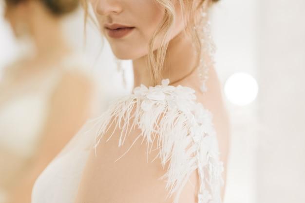 結婚式の日の詳細。羽のクローズアップと花嫁のドレスのドレス