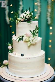 Трехъярусный свадебный торт со свежими цветами