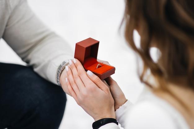 氷上の冬のラブストーリー。男は結婚指輪のクローズアップの手で女の子と結婚することを提供しています