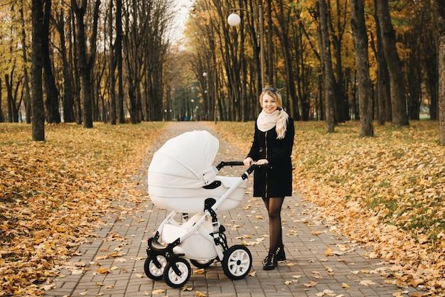 若い母親は、秋の公園で赤ちゃんと一緒に歩きます。白いベビーカーとママ