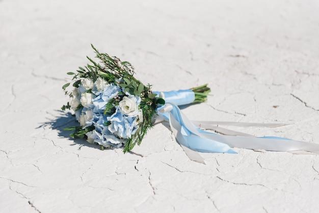 青いアジサイ、トルコギキョウ、ひびの入った白い長いリボンと緑の繊細なウェディングブーケ。青と白の結婚式の詳細