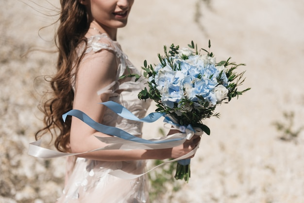 青いアジサイ、トルコギキョウ、花嫁の手に長いリボンと緑のおいしいウェディングブーケ。青と白の結婚式の詳細