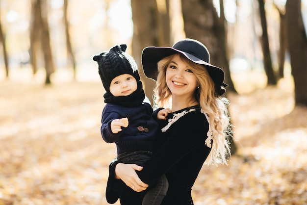 秋の公園で小さな子供を持つスタイリッシュな若いママの肖像画。