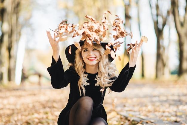 Красивая счастливая улыбающаяся девочка с длинными светлыми волосами, красными губами, в стильной шляпе, куртке позирует на осенней улице. открытый портрет, дневной свет. концепция женской осенней моды.