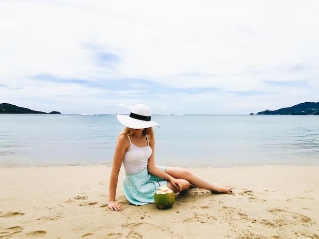 タイのココナッツと座っている青い海の海岸に帽子の若い魅力的な女性