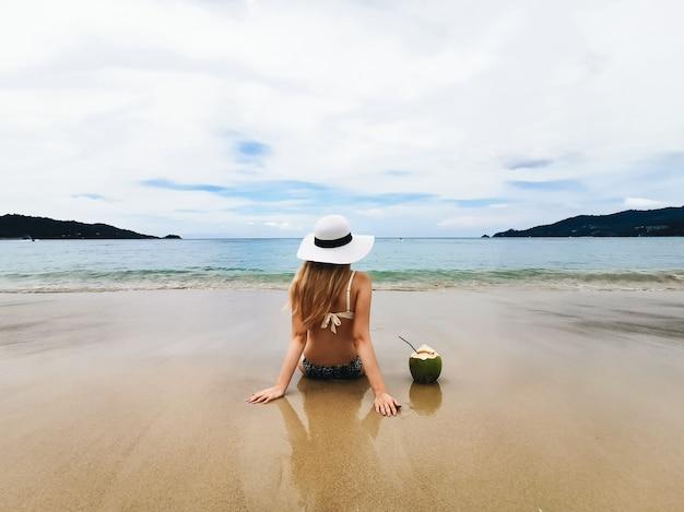 ココナッツ、タイに戻って座っている青い海の海岸に帽子の若い魅力的な女性