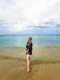 帽子と青い海の海岸にメガネの若い魅力的な女性を楽しんで、タイ