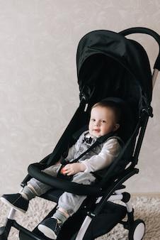 赤ちゃんバギーに座っている笑顔の少年