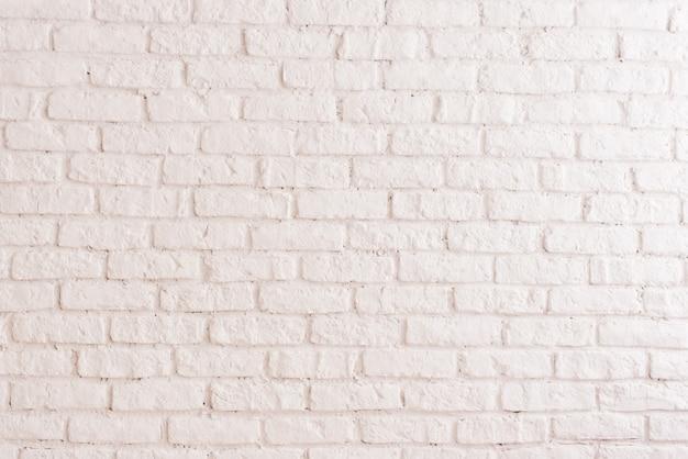 白い石膏水平テクスチャや背景を持つヴィンテージのレンガの壁。古い粘土レンガで作られた部屋のインテリアの白塗りの壁