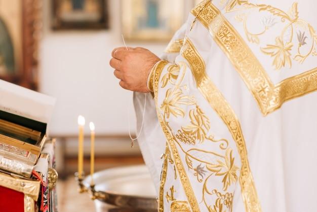 Священник зажигает свечу в церкви