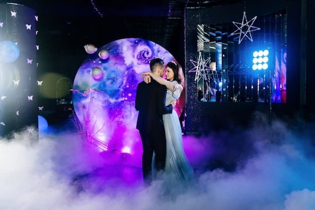 美しい光とアトスを備えたヘビースモークの驚くべき最初の結婚式のダンス。空間のスタイルで装飾。スペースウェディング