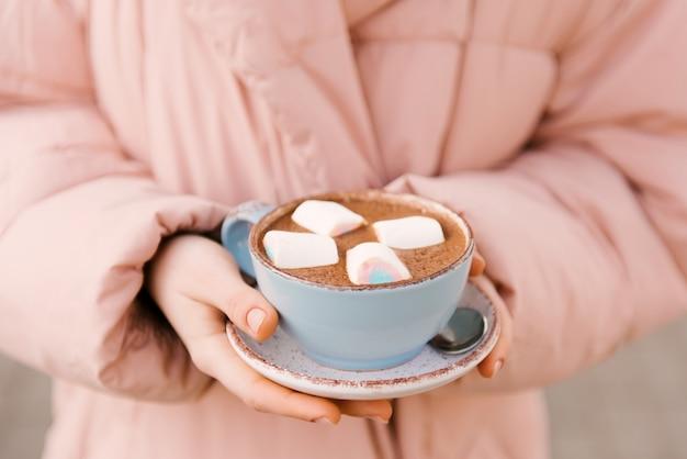 Чашка какао с зефиром в руках девушки в розовом пиджаке, детское меню, выборочный фокус