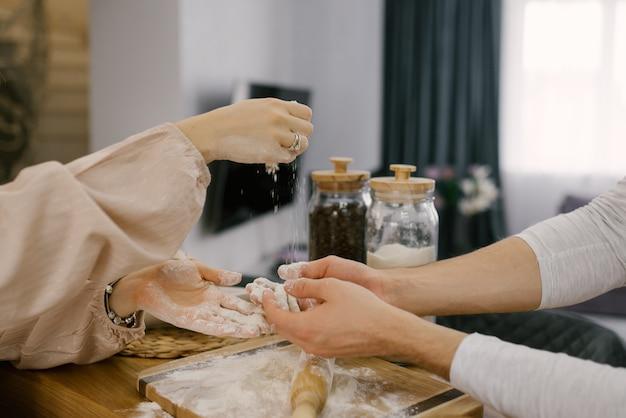 Руки парня и девушки готовят тесто, муку скалкой. выборочный фокус