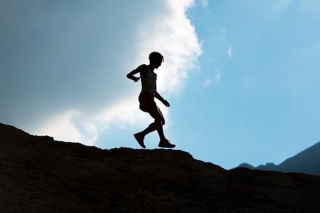 Женщина бежит вниз по горной тропе