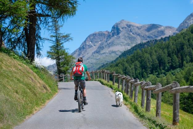 彼の犬の会社の山道でマウンテンバイクの男