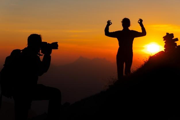 山の写真家はシルエットで日没のヨガのポーズの女の子