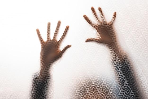 ガラスの壁に助けを求める女性
