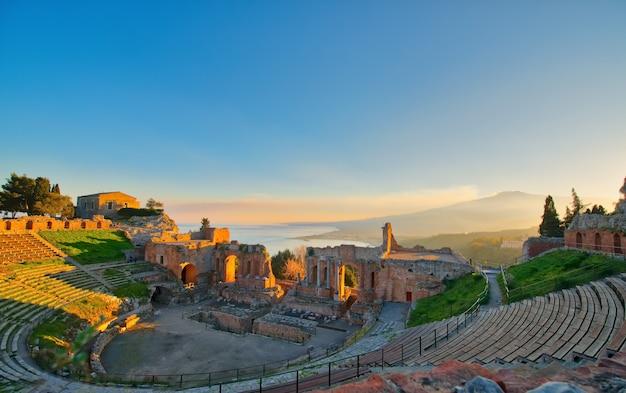 Древний театр таормина с извержением вулкана этна на закате