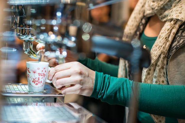 バーで女性がエスプレッソコーヒーを準備します