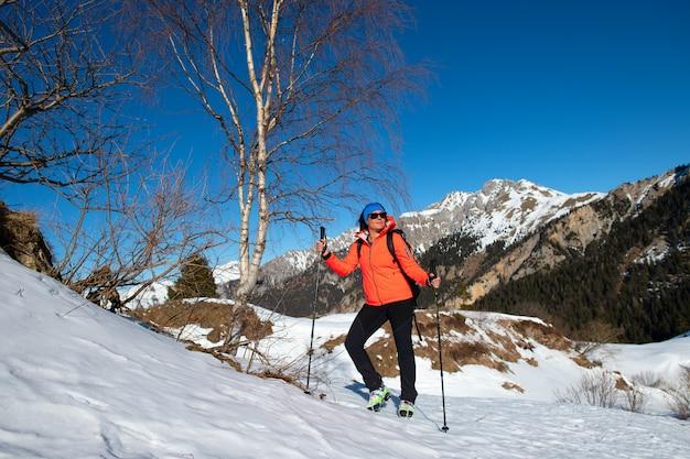 Женщина отдыхает и смотрит на вид во время прогулки в горах по снегу