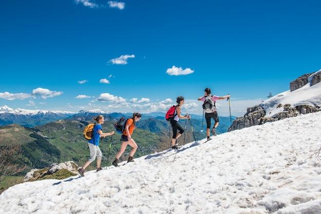 Группа девушек гуляет по снегу в горах, от радости.