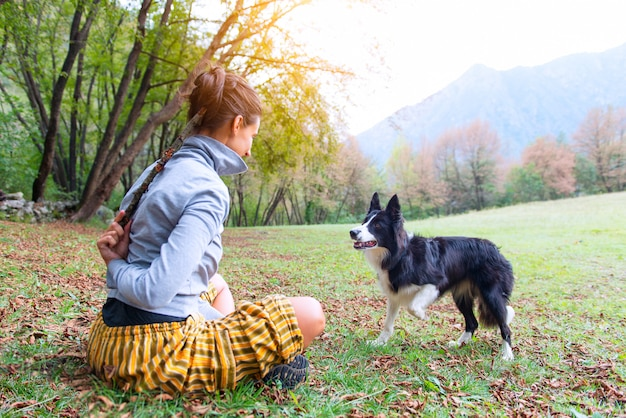 Девушка играет со своей собакой бордер-колли