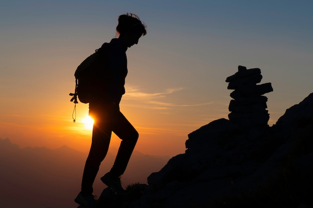 シルエットで山の中の女の子に向かっておとぎ話のような色で日没の遠足で