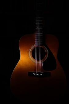 光や影の間の黒い背景にアコースティックギターの詳細