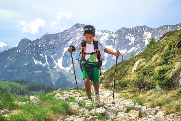 Маленький мальчик гуляет во время экскурсии по горной тропе с рюкзаком