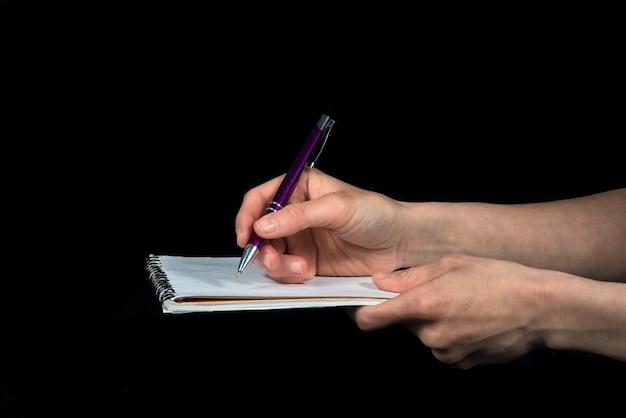 手が黒い背景にメモ帳でメモを取る