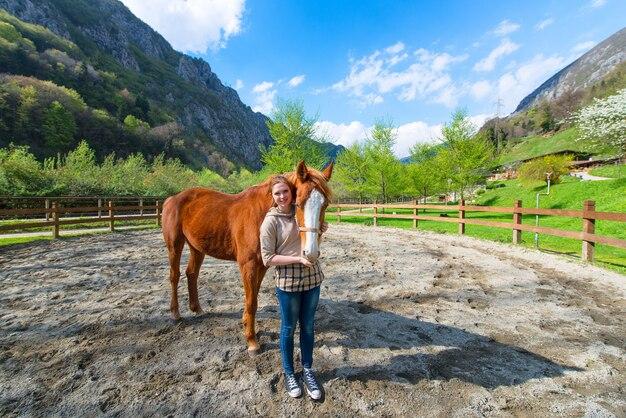 馬とパドックで立っている女の子。