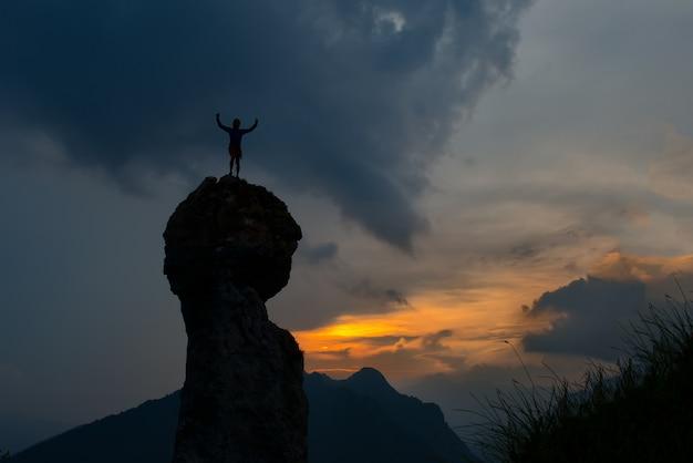 Человек покоряет вершину горы после трудного подъема