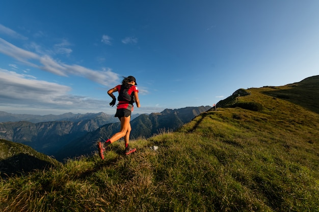 持久力トレイル中にスポーティな山の女性がトレイルに乗る