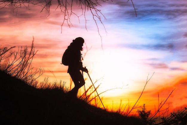 ダウンヒルシルエットでハイキングの女の子