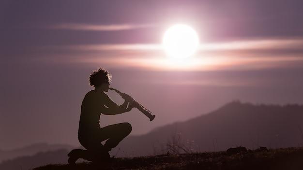 夕暮れ時の紫色の空のサックス奏者