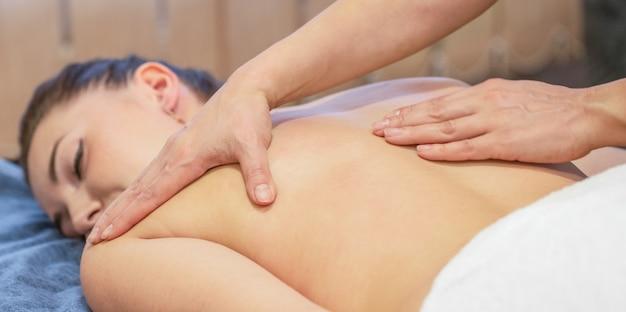 マッサージセラピストの手が少女の背中にマッサージをしています。