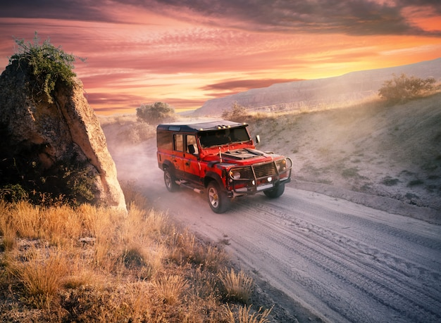 ほこりっぽい道に赤いオフロード車