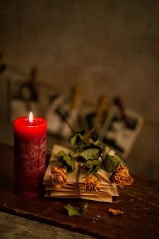 乾燥したバラのキャンドルと古い手紙の束のある静物