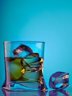ガラステーブルの上のウイスキーとアイスキューブとガラス