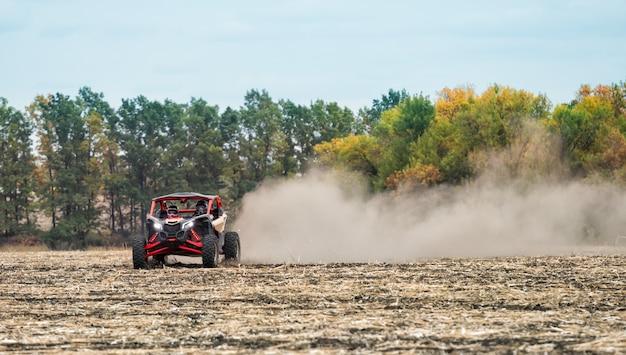 厚いほこりのクワッドバイクは、耕されたフィールドに乗る