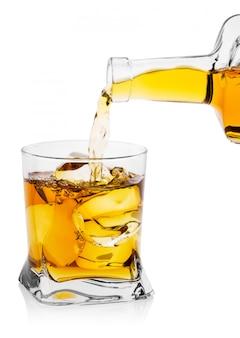 ウイスキーをボトルから氷で透明なガラスに注ぐ