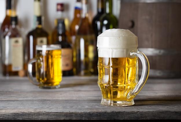 泡が付いている軽いビールの多面的なガラス