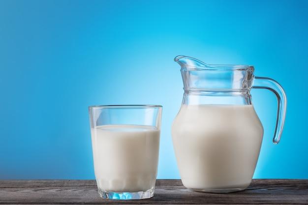 ガラスと木製のテーブルの上の水差しのミルク