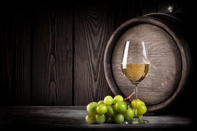 ガラスの白ワインとブドウの房