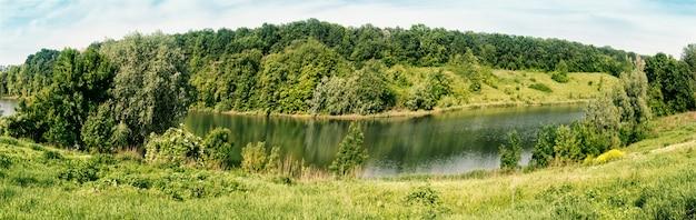 緑の木々や海岸の草で川のベンド