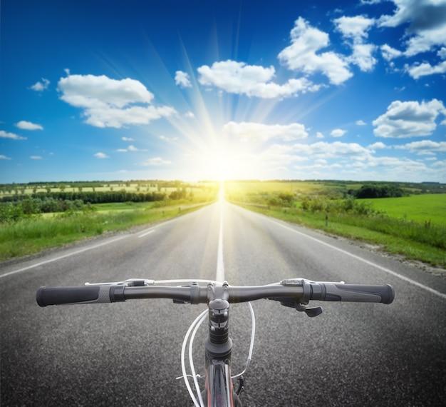 Велосипедный руль на дороге к яркому солнцу