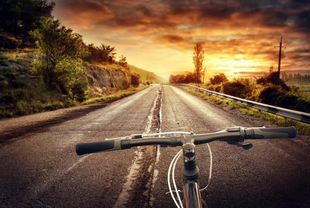 古いアスファルト道路の自転車の車輪