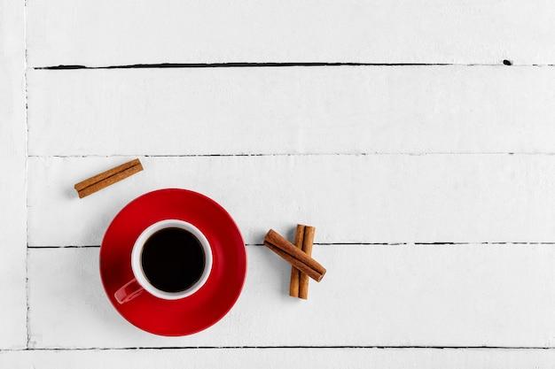 赤カップのコーヒーとシナモンスティック