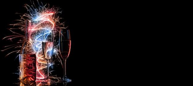 Бутылка и два бокала шампанского в разноцветных бенгальских огнях на черном