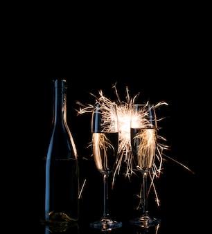 Бутылка и два высоких бокала шампанского в ярких искрах